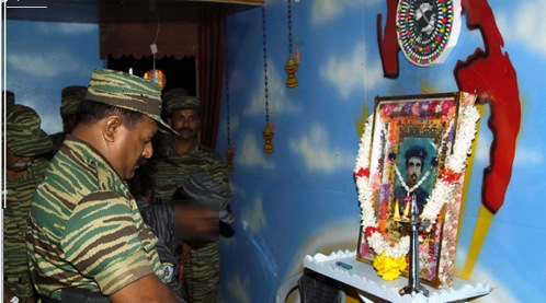 "Pirapāharan pays homage to black tigers,                                                                                                 Courtesy of TamilNet.com The picture on the wall is that of Miller (Vallipuram Vasanthan), who drove a truck laden with explosives into an army camp at Nelliyadi on 5 July 1987, the first LTTE suicide attack. Note the symbolism of flames and Miller's encirclement by flowers in keeping with a whole genre of ""circling rituals"" (ārati in Sanskritic Tamil) that are intended to remove unwanted negatives from a person or place. Other practices during Māvīrar Nal in November indicate that the māvīrar are symbolically encircled and protected by cosmic forces marked by the jasmine flower or glory lily. This is a Tantric principle that has been incorporated within Hindu orthodoxies without necessarily being recognised as Tantric."